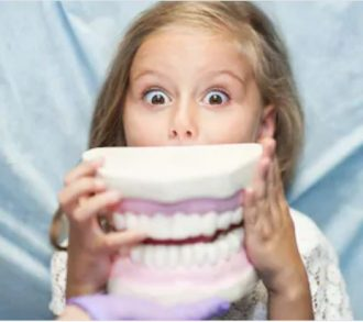 Child at dentist surprised looking at giant teeth